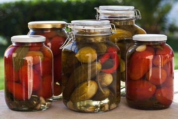 Glass jars of homemade canned tomatoes and cucumbers