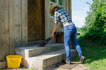 Cowgirl sweep stairs with wooden broom in rural