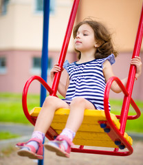 Young girl is swinging in playground