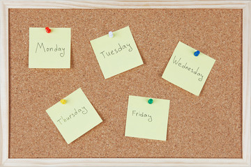 Post-it notes with weekdays sticked on corkboard