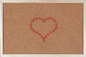 Heart made of pushpins on corkboard