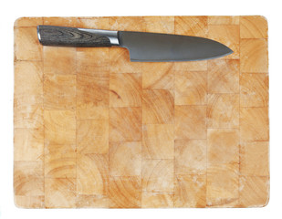 Kitchen knife laying on used chopping board