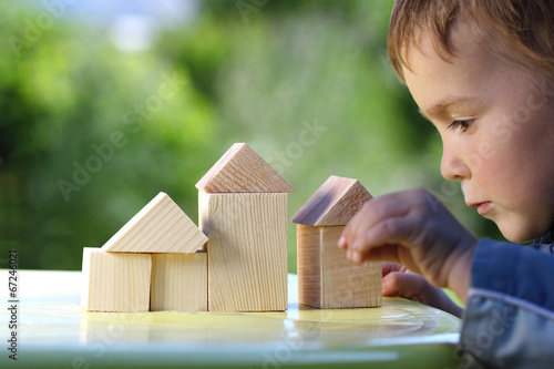 boy raises his hand to the house from wooden cubes - 67246021