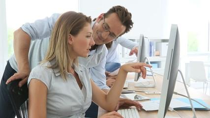 People in business training working on desktop computer