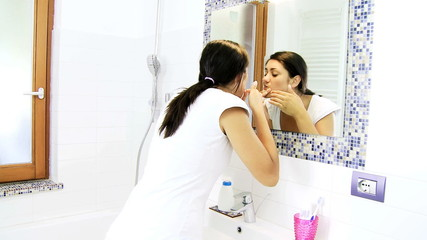 Woman checking skin problem in mirror