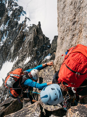 Young female climber helps another climber to reach the top of a