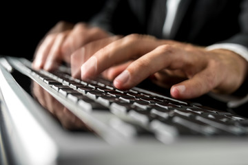 Hands of a man typing fast on a computer keyboard