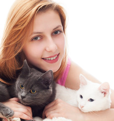 beautiful smiling girl hugging her two cats