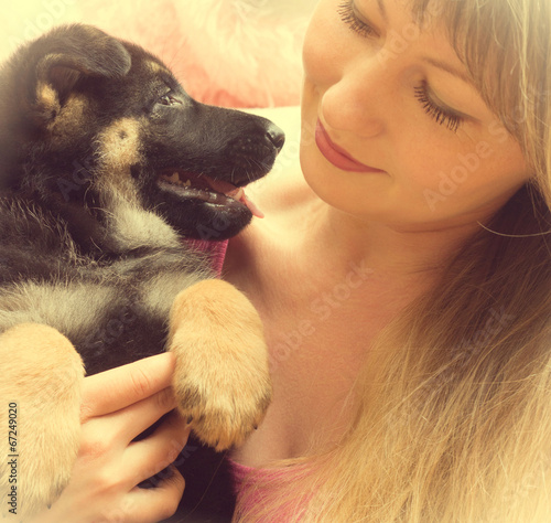 young woman holding a German Shepherd puppy