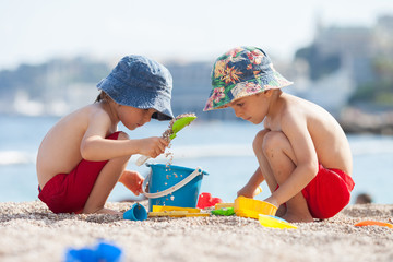Two cute kids, playing in the sand on the beach
