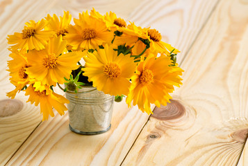 Yellow flowers in a pail on the wooden table