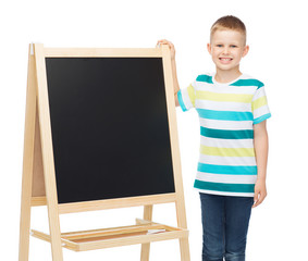 happy little boy with blank blackboard