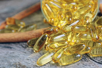 Cod liver oil omega 3 gel capsules isolated on wooden background