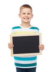smiling little boy holding blank black chalkboard