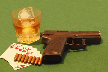 royal flush in poker table with a gun, a drink and bullets