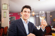Man holding a glass of white wine in a restaurant