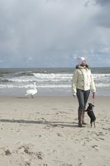Frau, Hund und Schwan am Ostseestrand