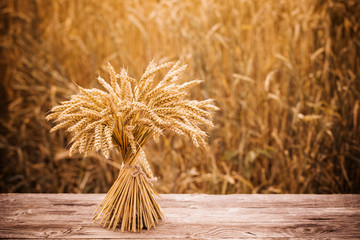 sheaf on wooden table on background field