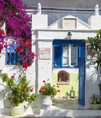 Architektur auf den Kykladen: Haus mit blauer Tür u Blumen