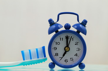 Miniature clock showing 7 am with blue toothbrush