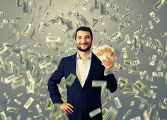 happy businessman standing under money rain