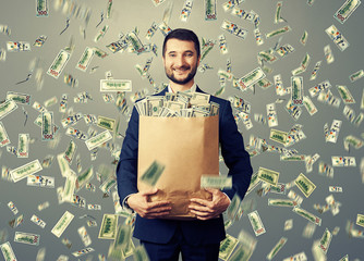 smiley businessman holding paper bag with money