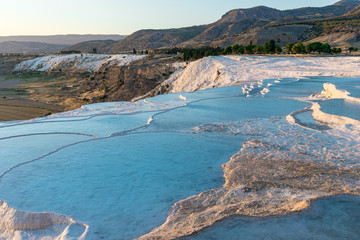 Carbonate travertines with blue water, Pamukkale, at sunset