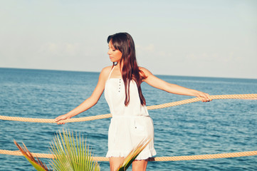 Girl with long hair in a short white dress on the pier