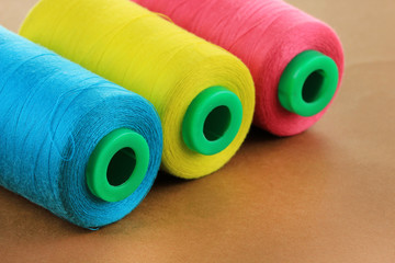 Colored bobbins on brown background