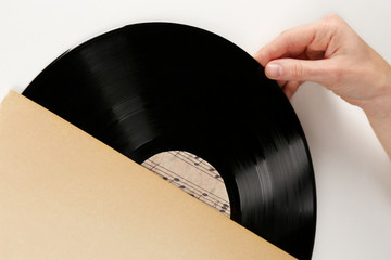 Hands opening old vinyl record, isolated on white