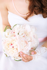 Bride holding wedding bouquet of white peonies, close-up,