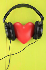 Headphones and heart on color wooden background