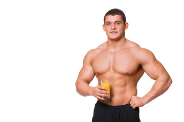 muscular sports man holding a glass of juice isolated on white