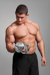muscular man working out with dumbbells on gray background