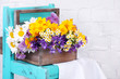 Leinwandbild Motiv Beautiful flowers in crate on small chair on light background