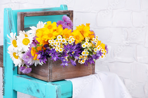 Leinwanddruck Bild Beautiful flowers in crate on small chair on light background