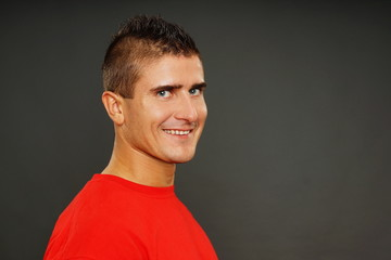 Portrait of young man in red shirt, right you can some text