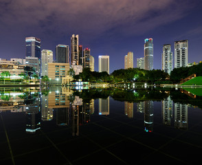 City park with modern buildings in Kuala Lumpur at night reflect