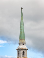 Old church spire against cloudy sky