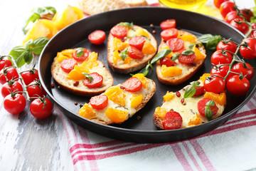 Tasty bruschetta with tomatoes on pan, on old wooden table