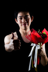 Asian boy with red bouquet in dark background