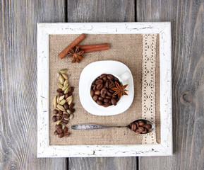 Wooden frame with white mug, coffee grains and spices