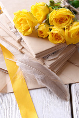 Old letters and flowers on wooden background close-up