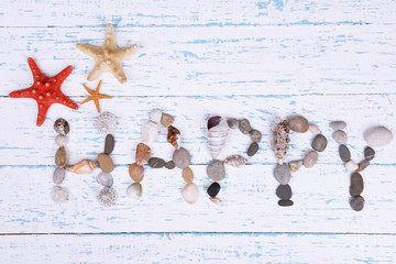 Word happy made from sea shells and stones on wooden background