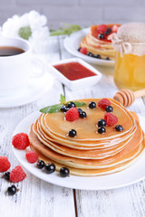 Sweet pancakes with berries on table close-up