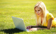 Blonde Girl with Laptop. Smiling Beautiful Woman Lying on Grass