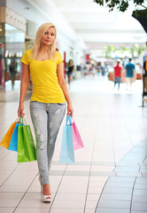 Shopping. Blonde Woman with Colorful Shopping Bags in Mall