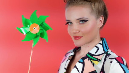Beautiful Blonde Model Holding Green Pinwheel On Red Background