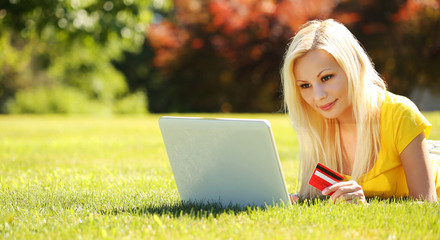Online Shopping. Smiling Blonde Girl with Laptop and Credit Card