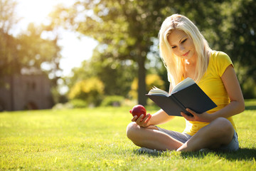 Blonde Girl with Book and Apple on Green Grass. Beautiful Woman